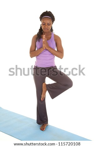 A woman taking a break and doing tree a yoga move on a mat.