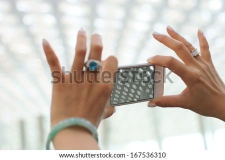 a woman taking photo with mobile phone in airport, shenzhen, china - stock photo