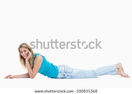 A woman talking on her mobile phone is smiling at the camera against a white background - stock photo
