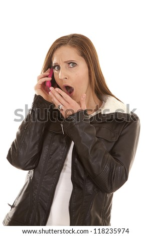 a woman talking on the phone shocked at what she is hearing. - stock photo
