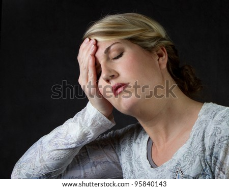 A woman that is upset, depressed or has a headache - stock photo