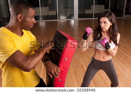 a woman trains with her trainer and is in a punching stance - stock photo