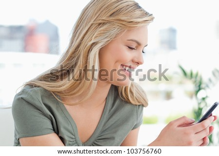 A woman turned to the side smiles as she uses her phone. - stock photo