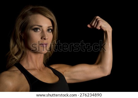 A woman up close, flexing her arm showing her toned muscles.