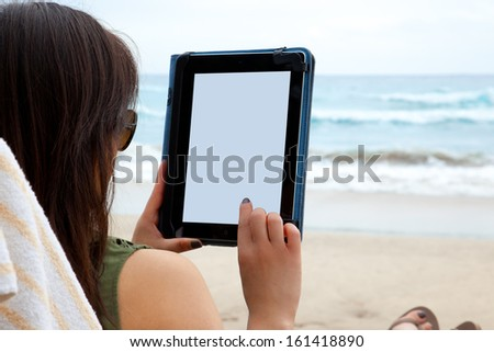A woman uses a tablet device while on the beach, symbolizing the ability to blend work and rest while working from anywhere. - stock photo