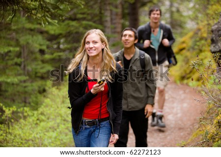 A woman using a GPS in the forest on a camping hike