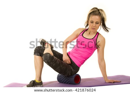 a woman using a roller to roll out her body after a hard workout. - stock photo
