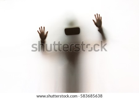 A woman using a Virtual Reality headset behind a white sheet. She's looking for a scape.