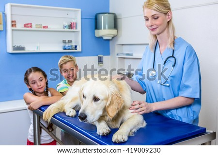A woman vet and children looking a dog on the operating table