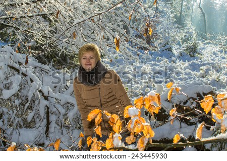 A woman walking alone in the forest covered in snow