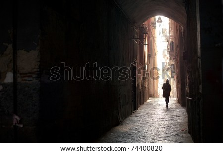 A woman walking alone under an acient arch of the greek downtown of Naples