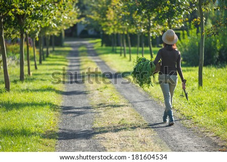 a woman walking home, carrying a basket full of vegetables