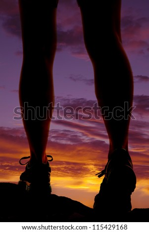 A woman walking in the sunset.  Silhouette of legs. - stock photo
