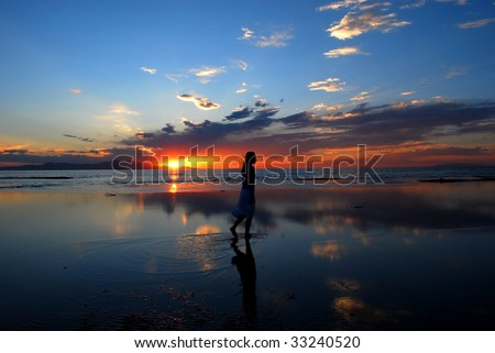 A woman walking in the water during a sunset - stock photo