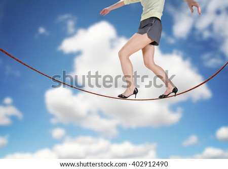 a woman walking on a tightrope made of string for the concept of risk or danger in the business corporate world isolated on a cloudy sky background - stock photo