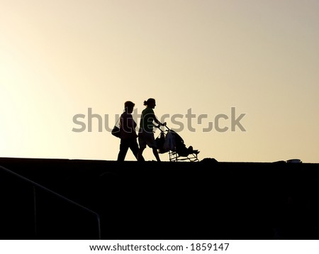 a woman walking whit child and grandmother at sunset