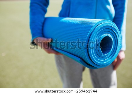 A woman walking with a yoga mat - stock photo