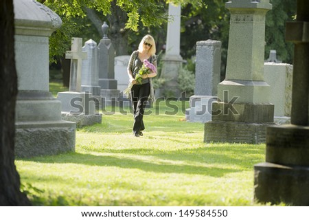 A woman walks through the cemetery with flowers - stock photo