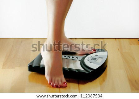 A woman wants to weigh and stands on the scales - stock photo