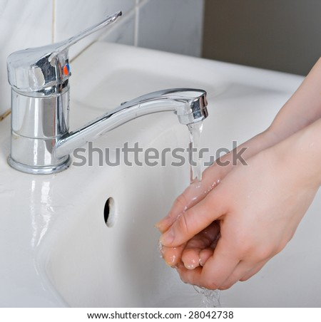A woman washes her hands under the faucet