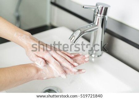 A woman washing hand on the sink