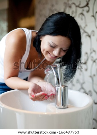 A woman washing her hands in the sink