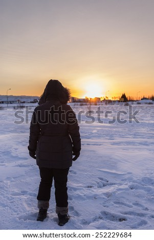A Woman Watching Sunrise in Winter - stock photo