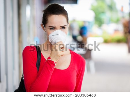 A woman wearing a face mask in the city coughing. - stock photo