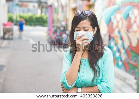 A woman wearing a face mask in the city coughing - stock photo