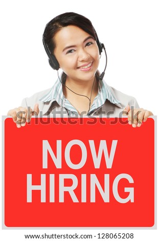A woman wearing a headset holding a sign on hiring - stock photo