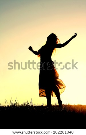 A woman wearing a long skirt, with long blonde hair, is dancing and praising God, while silhouetted against the evening sky - stock photo