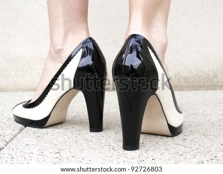 A woman wearing a pair of black & white classic high heels with clipping path. - stock photo