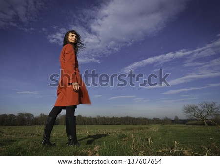 A woman, wearing a red coat, in a meadow on a windy day. - stock photo