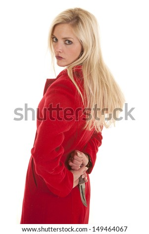 A woman wearing a red jacket is standing with a knife behind her back