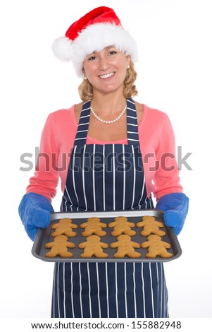 A woman wearing a Santa hat and apron holding a tray of freshly baked gingerbread men, isolated on a white background. - stock photo