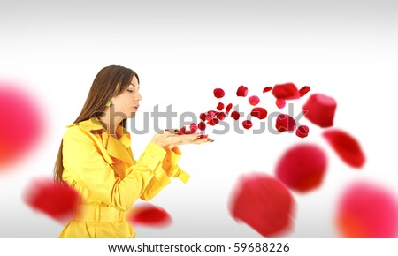 A woman wearing a yellow coat with petals blowing away. - stock photo