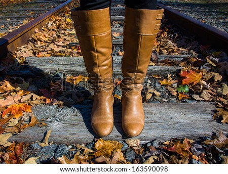A woman wearing boots stands on train tracks in the Fall.