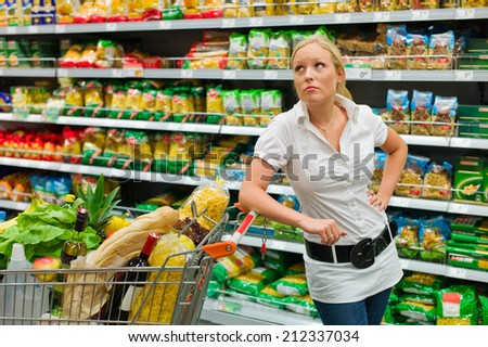 a woman when buying groceries in a supermarket. everyday life of a housewife - stock photo