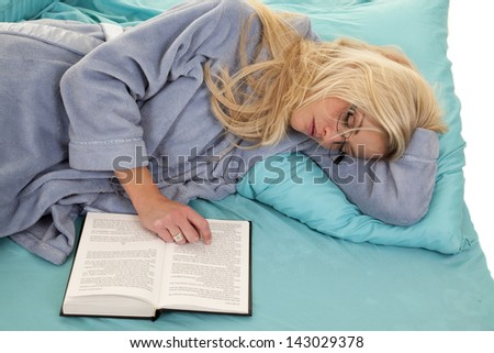 A woman who is asleep while she is wearing her glasses and her book open - stock photo