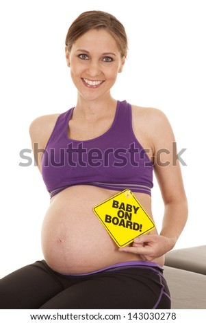 A woman who is expecting baby holding  a baby on board sign on her belly. - stock photo