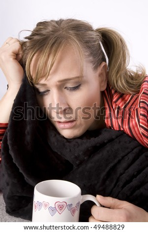 A woman who is sick holding her blanket and tissue looking into a cup with something warm in it to help her feel better.