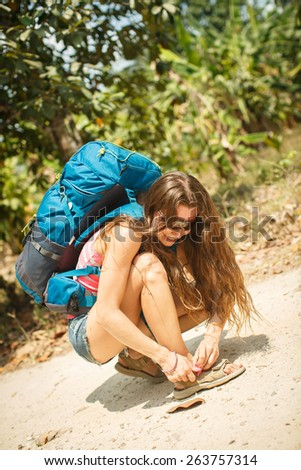 A woman with a backpack buttons sandals - stock photo