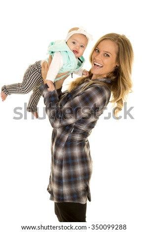A woman with a big smile and so does her baby while she is holding her up. - stock photo
