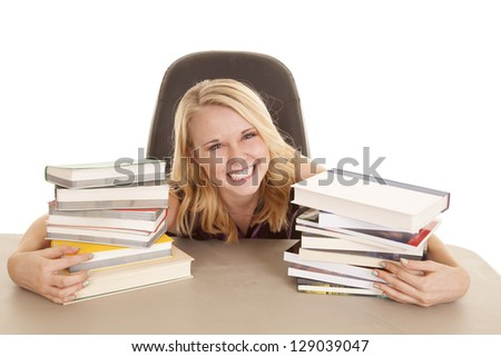 A woman with a big smile on her face holding on to her two stacks of books.