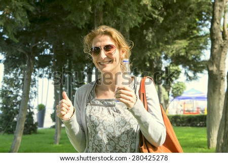 a woman with a bottle in hand in Sunny weather