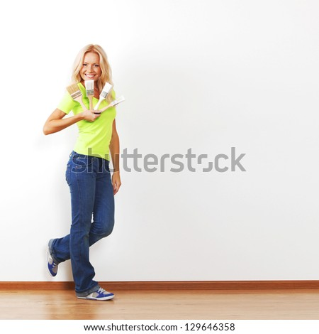 a woman with a brush against the wall - stock photo