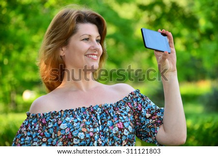 A woman with a cell phone in a pine park