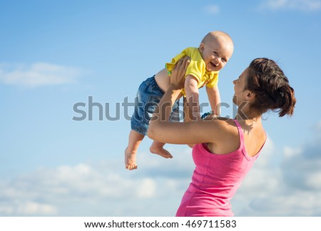 A woman with a child playing on the beach, mom with baby in nature