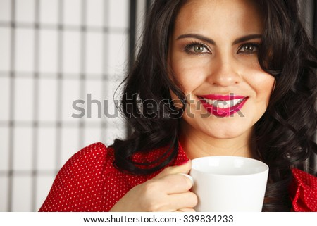 A woman with a coffee or tea cup.