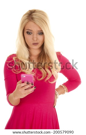 a woman with a confused expression on her face looking down at her phone. - stock photo